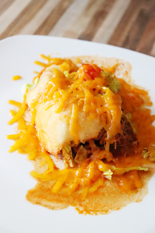 A New Mexican stuffed sopapilla with red chile and melted cheese