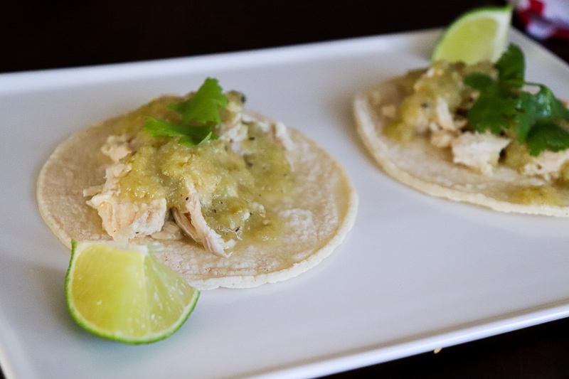 Salsa Verde Chicken Tacos on a white place with a lime wedge