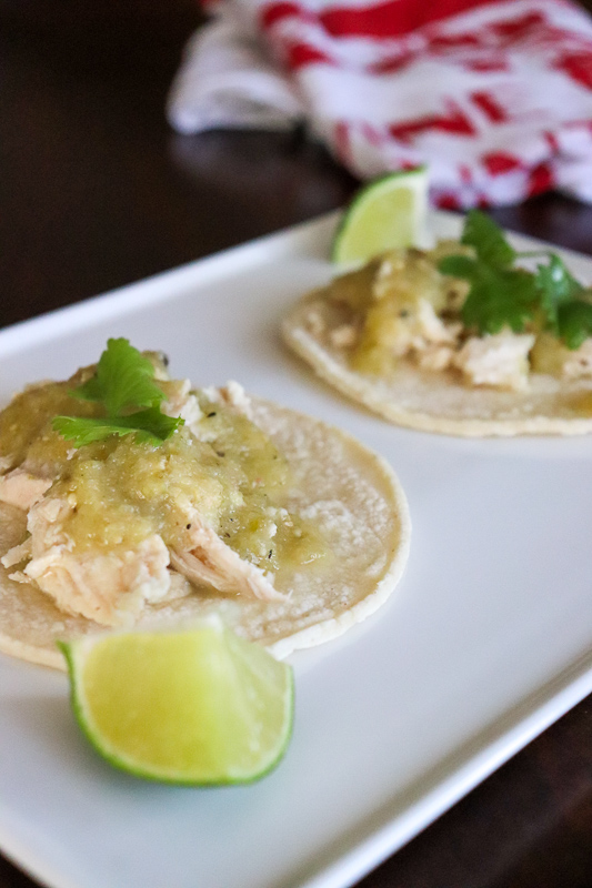 Salsa Verde Chicken Tacos on a white place with a lime wedge and a white towel